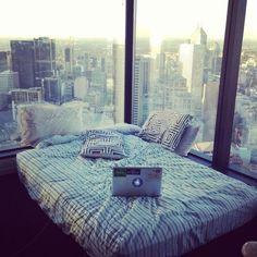 Instagram photograph of a bed with a rather great view over the skyline of Melbourne, Australia / taken by 'Kimmi Smiles'