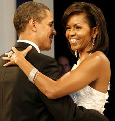 Barack and Michelle Obama dance arm-in-arm and smile. She wears a white dress, large ring, long earrings and a bracelet. He wears a black tuxedo.