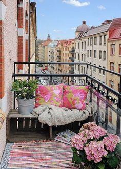 Un petit balcon aménagé avec des caisses en bois récup' pour remplacer le banc. Côté déco, il suffit de superposer quelques tapis colorés !