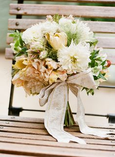 The gold and cream bouquet included cafe au lait dahlias, parrot tulips, lace cap hydrangea, ranunculus, passion vine, hellebores, blushing bride protea, wild grasses, and miniature pomegranate, accented with a gold brocade ribbon.