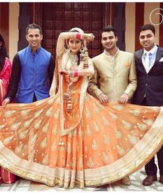 Indian bride with her brothers holding her orange lehenga