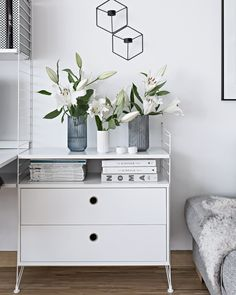white lilies and string furniture unit in a scandinavian apartment | my-full-house.com