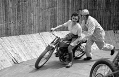 """Circa 1949, UK — Tornado Smith helps Maureen Swift ride a motorcycle around the """"Wall of Death"""" to promote BSA motorcycles."""