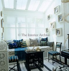 The conservatory has a black, white and blue colour scheme and an assortment of ethnic and blue and white vintage cushions scattered on the banquette ~ Hubert Zandberg in London UK