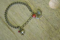 """Bracelet """"Exotique"""" en bronze et sa perle naturelle de corail, composé d'un globe et d'une feuille de ginko. #bijoux #bracelet #faitmain #ginko"""