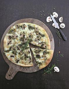 Recette Pizza blanche champignons-pesto : Préchauffez le four à 180 °C (th. 6). Préparez la pâte. Versez la farine dans un grand saladier. Formez un puits et versez-y la levure, trois pincées de sel et l'eau tiède. Mélangez à la main. Pétrissez environ 5 mn sur le plan de travail fariné...