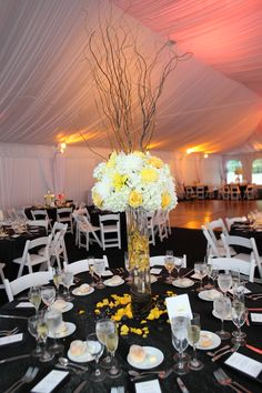 A bold, tall yellow centerpiece with branches coming up from hydrangea, roses and orchids, and submerged flowers in its base.