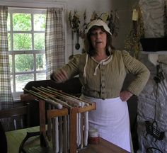 The lady of the house, Ulster American Folk Park, Omagh, Co Tyrone, Northern Ireland. Frequent craft demos are carried out in high season & reenactors in period costume, bringing the past to life.Here a demonstration of wax candle making.