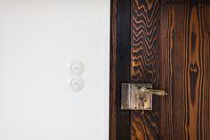 Neben den Lichtschaltern nach historischem Vorbild die aufgearbeiteten Türen mit den Original-Beschlägen, -Schlössern und -Griffen.