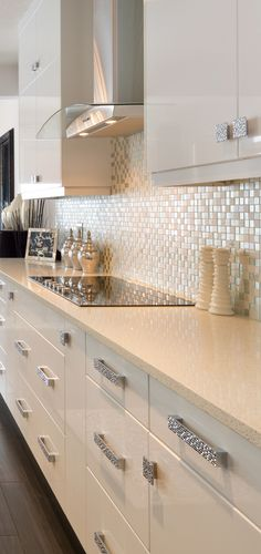 Sleek kitchen featuring a cream granite countertop, white cabinetry, a rounded chimney style hood fan and glittering hardware. Kitchen Hood Fan, Morrison Homes, Luxury Estate, Granite Countertops, Home Builders, Kitchen Remodel, Home Improvement, Sweet Home, New Homes
