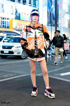 Layla's outfit this time includes a resale Home Depot jacket over a Killstar t-shirt, shorts from the Japanese brand Glad News, and Bubbles Harajuku platform sneakers. Accessories include earrings from Spinns, a vintage sun visor, and a Brooklyn Nets sackpack from the NBA.