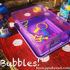 """Bubbles: """"We just held a Mega Messy Birthday party for my son's second birthday. We had seven different play stations set up and each cost less than $15. A favourite was the bubble station! A big container of cheap bubble solution poured into a shallow container with assorted bubble wands. The kids aren't struggling to get the wands out of a bottle without knocking it over and they can all dip and blow bubbles at the same time. Everyone loves bubbles!"""" — Danni and Mel of Honey You Baked"""