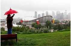 'Firehose of moisture' caused floods in Calgary ... A man records a view of the flooded Calgary Stampede grounds and Saddledome after heavy rains caused flooding, closed roads, and forced evacuation in Calgary Friday, June 21, 2013. Photograph by: Jeff McIntosh , THE CANADIAN PRESS