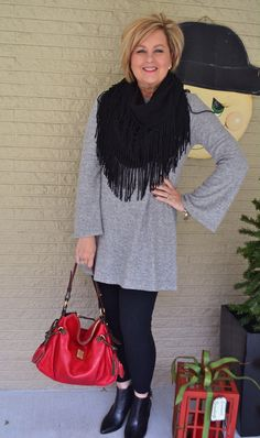 Love the look of the soft gray tunic sweater with black leggings, black booties, and fringed scarf - plus the lovely red pop of color in the handbag!