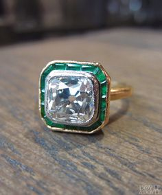 Antique Old Mine cut diamond ring with a frame of calibre emeralds in gold. From Doyle & Doyle.