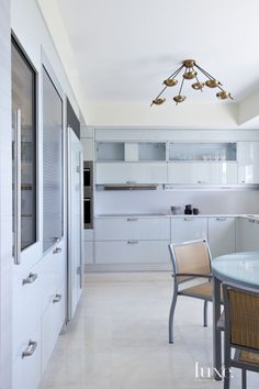 A sophisticated design pedigree makes its way into the sleek and serene kitchen, where Antonio Citterio's cabinetry for Arclinea recalls the color of seafoam and provides a clean, present-day contrast to a 1950s Stilnovo chandelier from Bernd Goeckler.