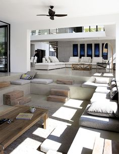 Living room in concrete, wood, and white with lowered sofa area via Planete Deco