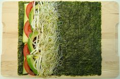 Rouleaux nori de légumes : 4 feuilles d'algues nori, 1 avocat, 1 concombre omyen, 2 carottes, 1 tasse de chou, sauche Tamari, eau. Couper les légumes en bâtons un peu plus courts que la feuille nori. Rouler les légumes dans l'algue (laisser de la place en dessous pour fermer). Tremper ses doigts dans l'eau et les mettre sur tout le socle du rouleau.