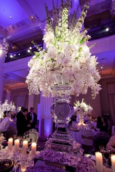 The couple's wedding reception was illuminated with ambient violet lighting. A unique centerpiece in the center of the head table featured a vase carved out of ice topped with vanilla blooms and white orchids. #centerpiece #flowerarrangement #icesculpture Photo by Michael Carr Photography