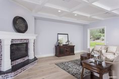 Exposed brick fireplace, beautiful wood floors, coffered ceilings