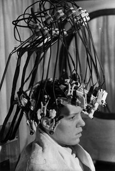 """This is what you might call an old-fashioned approach to a perm. Here, a woman at Em Westmore's beauty salon has her strands coiled in an electric permanent wave machine, which was used on long hair of the time. Westmore's MO was turning every gal from a """"chairlady"""" to a """"glamour girl.""""   - MarieClaire.com"""