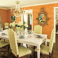 Try a nontraditional color scheme. This formal dining room jazzes up a traditional foundation with unexpected color combinations. The graphic green upholstered chairs play off of the distinctive orange-and-gold wallpaper. Gilded accents pick up the metallics in the pattern of the paper.