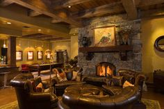 Game room/man cave. I like the fireplace feel, and wooden beams with leather furniture.