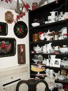 Kitchen shelves.  White dishes and floral trays.