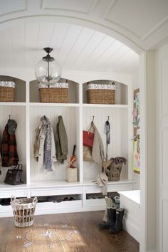 Cute mudroom. I love that the unit is built into the wall and not a separate piece sticking out. baskets/coat hangers for each child.