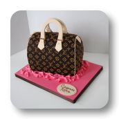 This cake was sculpted to replicate a high end hand bag. The LV pattern was hand piped and everything is edible!