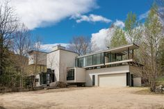 This impressive modern house designed by Mack Scogin and Merrill Elam Architects perches on a 2.86-acre sloping site in Stoneham in western Maine.