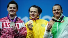 Svetlana Podobedova of Kazakhstan celebrates on the podium with her gold medal, Natalya Zabolotnaya of Russia (L) the silver and Iryna Kulesha of Belarus (R) the bronze, following the women's 75kg Weightlifting final on Day 7