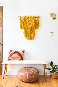 The mustard macrame piece was found on Etsy, made by Woven Whale. The bench underneath it was built by James.