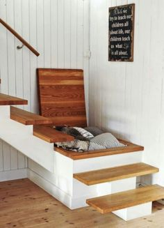 a hidden storage bin in the landing of the stairs for blankets for guest staying over or cold cozy nights on the couch.