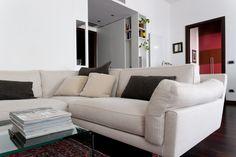"""Dettaglio divano: in evidenza la finitura in stoffa con trama """"disegnata"""". Sullo sfondo si intravede il mobile guardaroba posizionato in ingresso."""