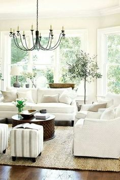 Remodelaholic | Budget Friendly Modern Farmhouse Family Room Makeover neutral decor with green accents, Potted Olive tree and Beautiful black wrought iron chandelier.