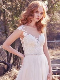 Maggie Sottero - SONJA, Delicate lace appliqués float over the bodice, plunging sweetheart neckline, and illusion cap-sleeves in this ethereal A-line wedding dress. A dazzling bead and Swarovski crystal belt and illusion open back trimmed with lace appliqués evoke subtle glamour. Finished with covered buttons and zipper closure.