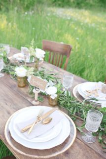 Olive leaf garlands on tables with single white flower buds in amber vases