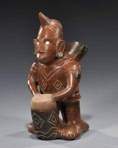 "Colima Shaman Drummer : Mexico, ca. 200 BCE - 300 CE. Terracotta standing shaman with mask-like face playing a drum; wearing a tunic with incised designs, having shell-inlaid eyes. Horn on forehead indicates that he is a shaman. 11-1/2""T x 6""W."