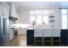A blue kitchen island with open shelves topped with white quartzite countertops is lit by glass and nickel lanterns highlighting three white and gray trellis slipcovered counter stools.