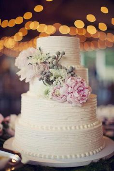 This wedding cake appears to have a butter cream frosting. I like the little dot decorations, and the muted color fresh flowers are lovely.