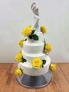 Tabler Hochzeitstorte mit echten Rosen und Porzellanbrautpaar. Der 1. Stock ist eine Schwarzwälder Kirschtorte, der 2. Stock ist gefüllt mit Joghurt-Sahne und Heidelbeeren, der 3. Stock mit Schokosahne und der obere Stock ist gefüllt mit feiner Walnusscreme.