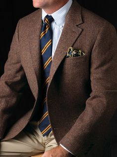 Brown sport coat, white shirt with light blue check, navy tie with yellow & red stripes, khakis