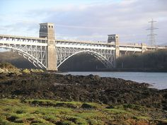 Brittania Bridge Train crossing - across the Menai Strait from the island of Anglesey and the mainland of Wales;  this 1972 two-tier truss arch bridge replaced an 1850 tubular iron bridge after a fire destroyed it;  trains cross on the lower deck, with road traffic on the upper deck;  it is 1,512 feet long and 40 feet high;  its longest span is 460 feet;  photo by Velela, via Wikipedia