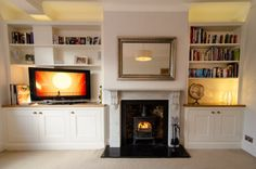 Gorgeous white sitting room - fireplace bookshelves television mirror cupboards