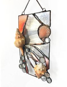 Mixing stained glass with organic found shells to create a piece of art that merges the beauty in nature with the beauty man can create. This sun catcher is hand cut and soldered with a copper patina incorporating found conch shells and a scallop shell. Would be great in any beach themed
