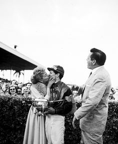 Lucille Ball kisses the winning jockey at the Tropical Park Race Track in Miami as her husband, Desi Arnaz looks on, 1956.