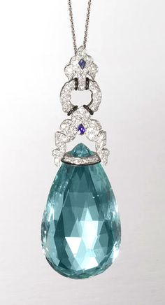 """An art deco aquamarine, diamond, sapphire and enamel pendant, by Marzo, circa 1925 The """"Hindoo"""" inspired surmount pavé-set with single-cut diamonds, decorated with fine bands of black enamel and two fancy-cut sapphires, suspending a large pear-shaped aquamarine briolette, mounted in platinum, signed Marzo Paris, length 7.5cm"""