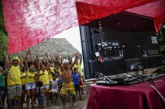 Brazilian Satere-Mawe indigenous peopel celebrates as they gather to watch the FIFA World Cup inaugural match between Brazil and Croatia, on June 12, 2014 in Manaus, Amazonas state, Brazil. AFP PHOTO / Raphael Alves (Photo credit should read RAPHAEL ALVES/AFP/Getty Images)