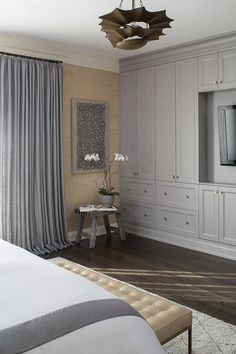 Master bedroom features a wall of gray built-in cabinets adorned with polished nickel knobs surrounding a flatscreen TV niche situated across from the bed.